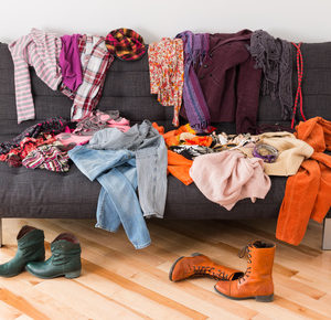 What to wear? Messy colorful clothing on a sofa.