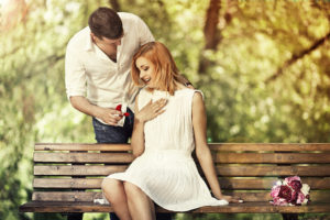 Man holding red box with ring making propose to his girlfriend outdoors.